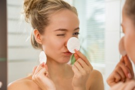 Young beautiful woman cleaning her face skin with cotton pad in bathroom. Standing in towel, looking in the mirror, laughing and having fun. Morning skincare routine.