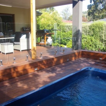 New merbau timber deck and covered alfresco area surrounding new swim spa with inset lighting, brushed fencing and stunning glass balustrade.