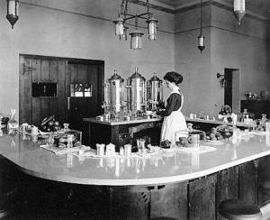 """A """"Harvey Girl"""" pouring coffee in lunchroom at Lamy, New Mexico, in early 1910's. Photograph from Northern Arizona University."""