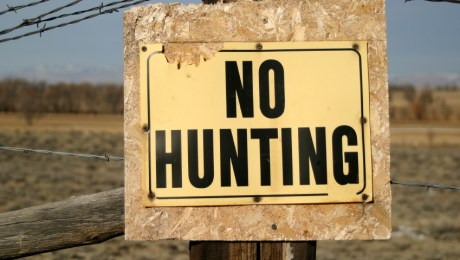 A beat up and weathered yellow No Hunting sign on a wood post complete with barbed wire.