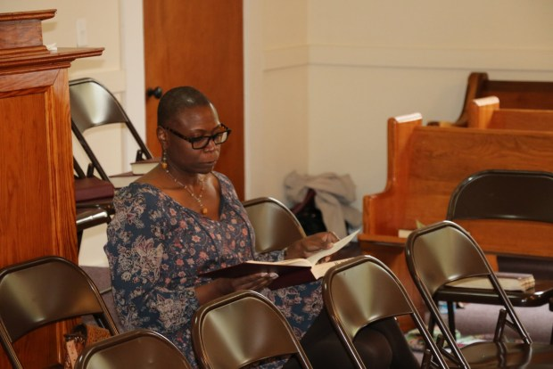 During recess, Bridgett Hill Kennedy studies her copy of The Sacred Harp. This contemplative individual portrait stands in contrast to the almost overwhelming amount of activity in the previous image. Photograph by Robert Chambless, taken at the Georgia State Convention, March 26, 2016, Big Creek Primitive Baptist Church, Alpharetta, Georgia [image 234 of 349].
