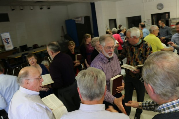 The parting hand. The square once again dissolves into individual one-on-one interactions, as we prepare to move from our community of singers back to the wider world. Photograph by Robert Chambless, taken at the Rogers Memorial Singing, March 6, 2016, Ephesus School, Roopville, Georgia [image 348 of 372].