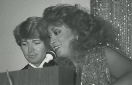 Mr. Gay All-American Emeritus (1984) Ron East and Miss Gay America 1974, the Lady Baronessa Maria Andrea del Santiago at the podium. No notes are on the photo, but if I were to venture a guess, there is a high likelihood that the duo is emceeing preliminary competition at either Miss Gay America 1983/84 or Mr. Gay All-American 1984/85, both held in Oklahoma City.