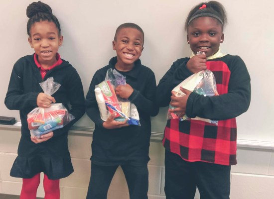 3 second grade students from Woodford Paideia Elementary School in Kennedy Heights proudly hold Veteran's Day hygiene bags.
