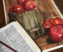 My latest painting of red, shiny apples with my open Bible.