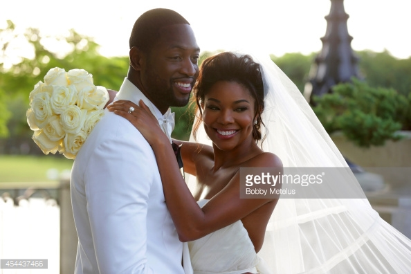 MIAMI, FL - AUGUST 30: Dwyane Wade, wearing customized Dsquared2 Tuxedo, his personally designed Wedding Collection bowtie from The Tie Bar and a boutonniére by Floral Fix and Gabrielle Union, wearing a Dennis Basso gown pose in this offcial wedding image on August 30, 2014 in Miami, Florida. (Photo by Bobby Metelus/Getty Images)