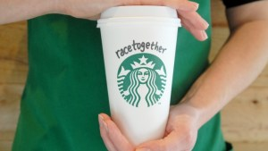 A Starbucks holding a cup with #RaceTogether written on it.