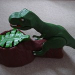 Click and push Dinosaur back (batteries fit in the underside of base)