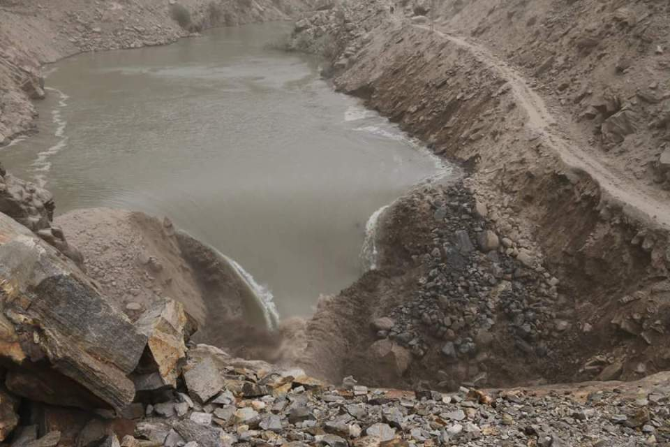 Water starts gushing down through the spillway as the debris gets erods