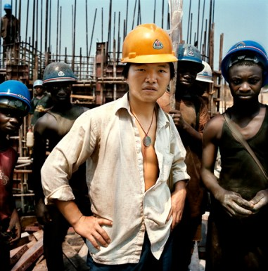 Republic of the Congo / Imboulou dam / 06.2007 On the building site of the Imboulou dam, Republic of the Congo, 200km north of the capital Brazzaville. In the foreground a Chinese worker of the China National Mechanical & Equipment corporation (CMEC) company, which in 2001 has obtained the contract. With its 120 megawatts, this power plant will double the national production of electricity and will give light to a large part of Congo. 400 Chinese technicians and qualified workers supervise a Congolese workforce of a thousand man, paid 3 dollars a day, that disappear as fast as they can find a better paid job. This, in part, explains the dam's construction delay that has to be absolutely terminated by 2009, the year of the next Congo elections. CMEC requires the Chinese workers to wear yellow and the Congolese blue hardhats. © Paolo Woods / Anzenberger
