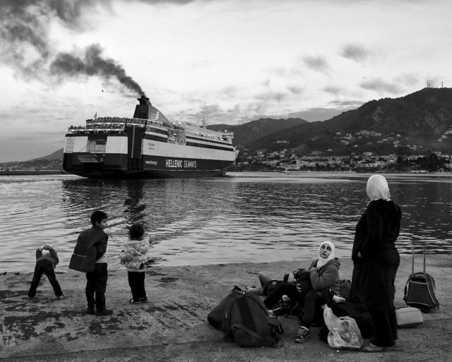 A Syrian family watches a ship leaving the port of the Aegean island of Lesbos as they wait to board on a next one bound to Piraeus port in Athens, on April 30, 2015.