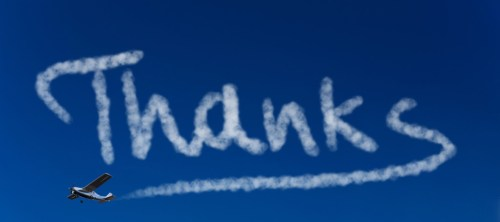 Skywriter writing the word Thanks in the blue sky