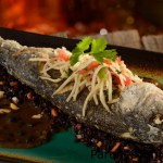 Disfruta la experiencia de la fusión de sabores en nuestro pescado sustentable frito entero al estilo asiático. Un pescado frito entero cubierto con ensalada de chile y papaya cortada en juliana, servido en una bandeja rectangular glaseada sobre una salsa de frijoles negros fermentada