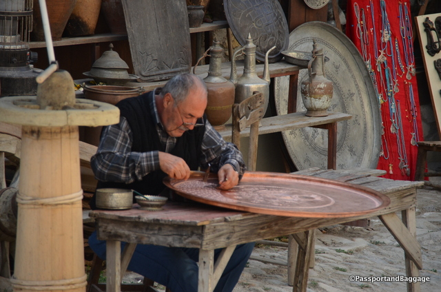 A coppersmith decorating one of the many trays you will find for purchase in the area.
