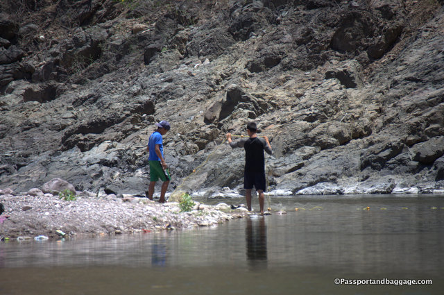 Boys trying to spread a net across the shallow river for fishing.