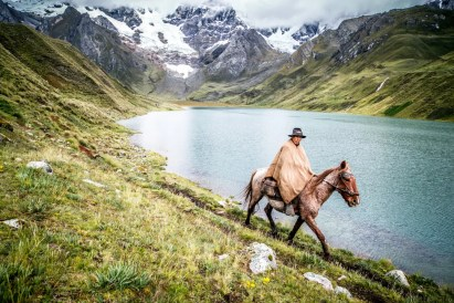 A gaucho rides along the shore of a lake high in the Cordillera Huayhuash, Peru