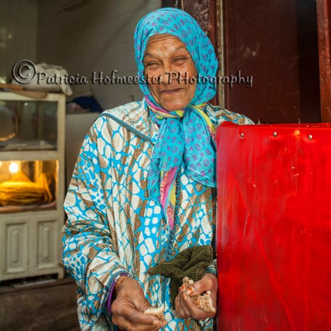 Smiling elderly lady with bread in the souk of Fez in Morocco