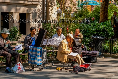Band of Chinese men playing music in a park in Chinatown, New York in the sun