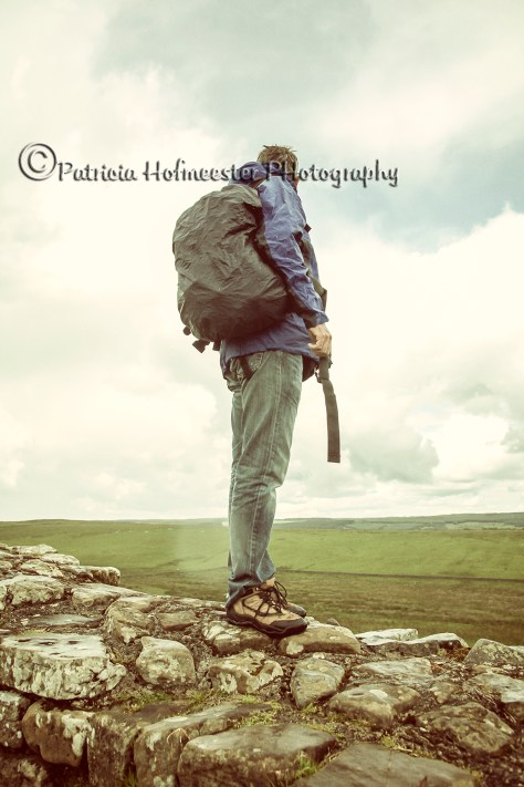 Hiker on the Hadrian wall in rain admiring the view
