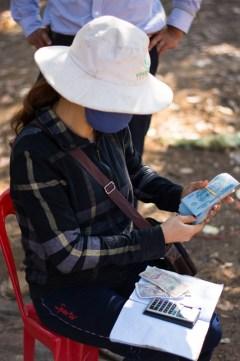 Cette femme collecte les noix de cajou et les garde jusqu'à l'arrivée des camions de ramassage - Là elle paie un saisonnier qui vient de lui apporter un sac de noix de cajou - http://paysansdavenir.com/plongee-au-coeur-de-la-filiere-noix-de-cajou-de-binh-phuoc-vietnam/