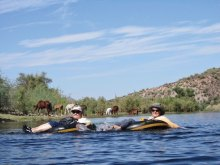 Wild Horses provide a picturesque background for this photo of PC Singles Club members Jackie Havranek and Rosemary Vana during one of the more peaceful moments of their recent tubing trip on the Salt River.
