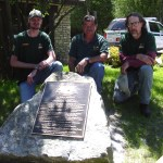"""Maintenance staff Eric Harabes, Roger Pronschinseke and Ben Wild pose by the newly installed bronze plaque that commemorates Peninsula's status as a """"centennial park."""""""