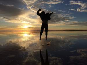 silouhette of person jumping above water, with sunset in the background