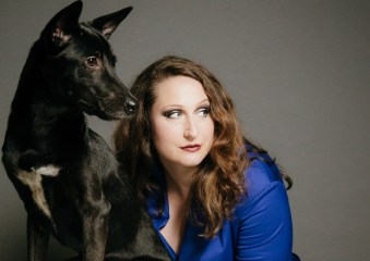 Black dog and woman in blue shirt looking to one side. Image for the production 'Bitch' as part of Brisbane Festival 2017