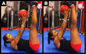 Woman works out abs by crunching to toes with ball.