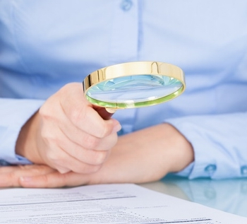 Businesswoman Looking At Document Through Magnifying Glass