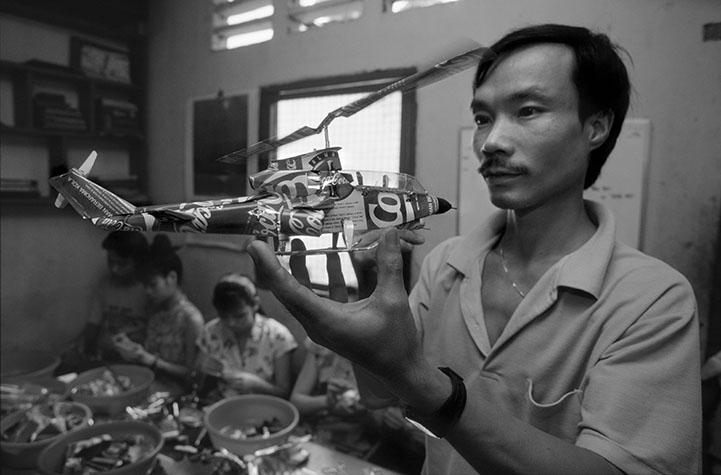 VIET NAM. This man runs a small facotry that fabricates helicopters and fighter planes from discarded soft drink cans, with the Coca-Cola helicopter being his best seller. Originally customers were tourists but nowadays he ships to shops all over the world.