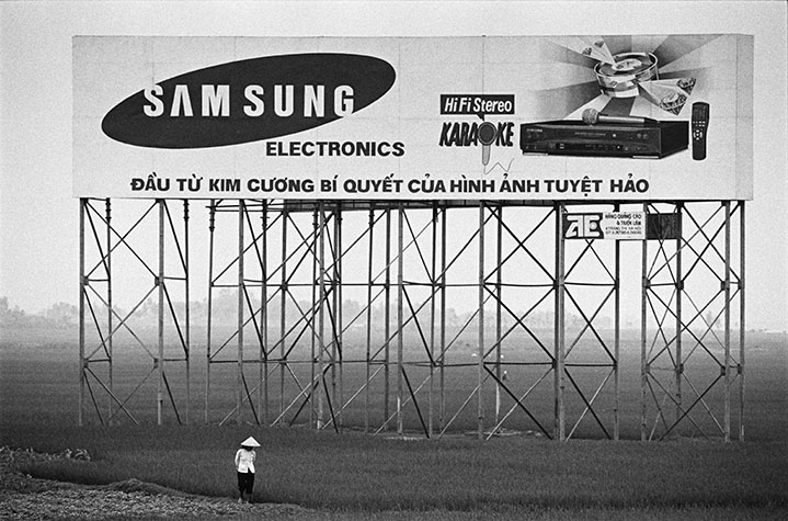 VIET NAM. Near Ha Noi, billboards nowadays cast a shadow over the rice fields.