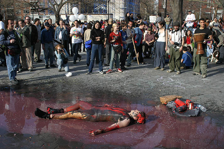 USA. New York City. March 22, 2003. Demonstration against war in Iraq. Street performers covered in blood and oil as protestors march down Broadway to Washington Square Park.