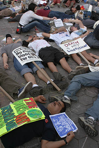 USA. New York City. March 22, 2003. Demonstration against war in Iraq. Demonstrators perform a lay-in as protestors march down Broadway to Washington Square Park.