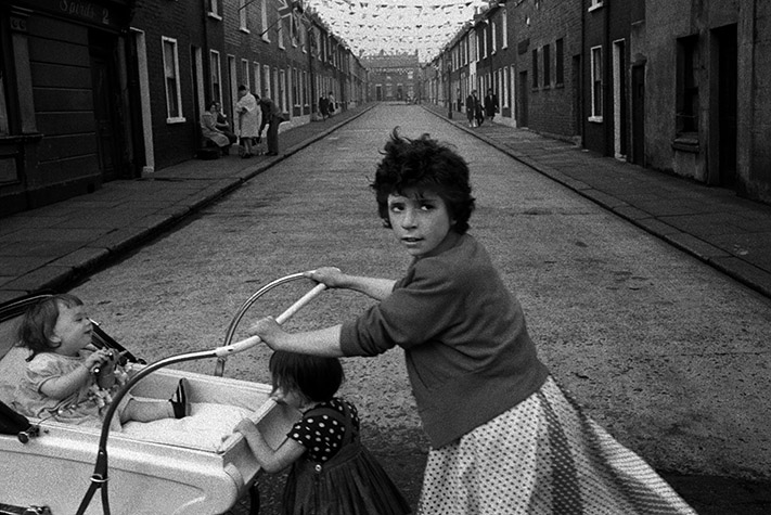 In the narrow terraced streets built for the working people of Northern Ireland (every house except the last needs only three walls), the closely knit communities of differing religious persuasions are encouraged to battle one another. Northern Ireland. 1965