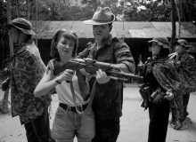 VIET NAM. David CHRISTIAN teaching his daughter to fire an AK47 rifle in a shootinng range at the Cu Chi tunnels, standing among models of the people he fought against.