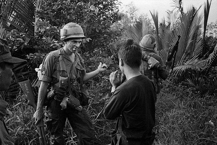 VIETNAM. US 9th Division troops on patrol in the Mekong Delta during a conversation with a peasant boy. 1967