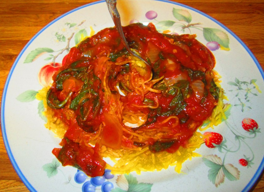 A slice tomato, tomato sauce, onion, and spinach sauce coated the top of the spaghetti squash noodles.