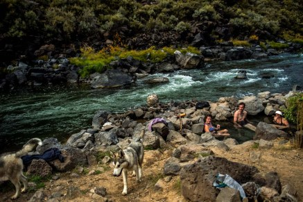 Visitors relax in the 99 degree water of the Manby Hot Springs along the Rio Grande River in Arroyo Hondo