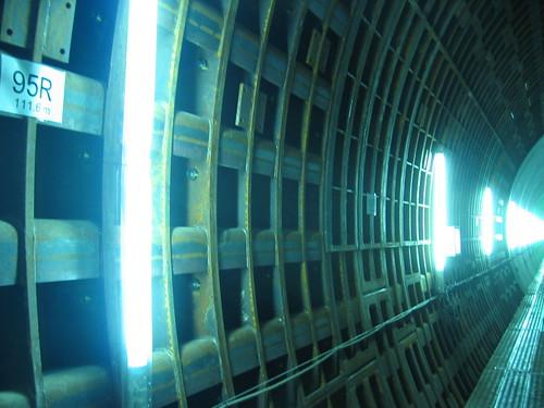 tokyo underground tunnel, bright neon on the raw metal walls