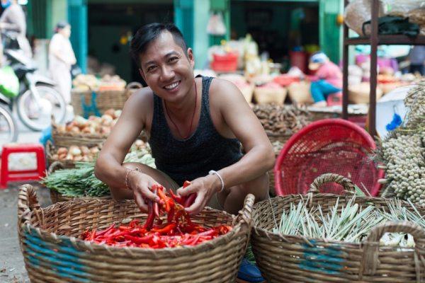 Lächeln verkauft ein asiatischer Mann auf dem  Straßenmarkt rote Chilischoten