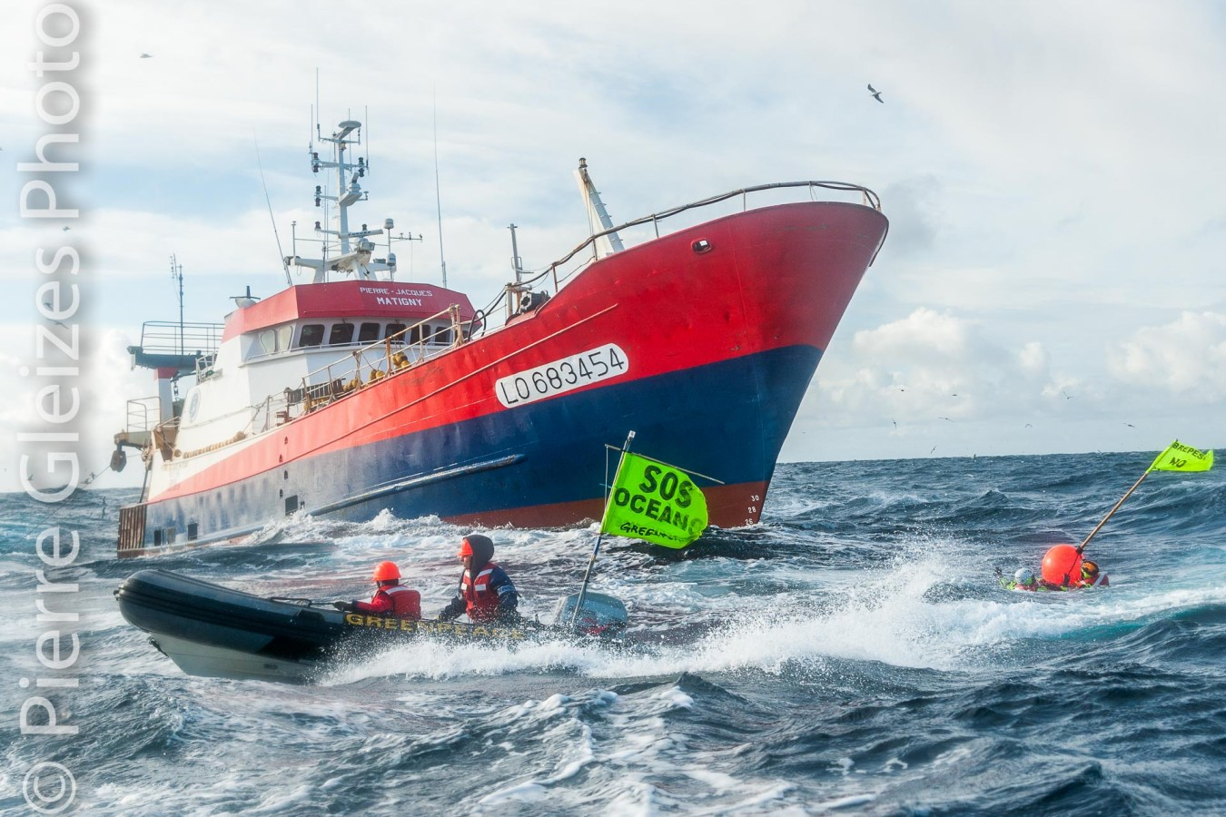 "Action de l'equipage de l'Arctic Sunrise de  Greenpeace a 60 km au large de l'Irlande pour protester contre la peche au chalut par 1000 metres de fond. Les militants se sont mis a l'eau devant le bateau chalutier francais Pierre Jacques Matigny de Lorient travaillant pour la Scapeche, fournisseur des magasins Intermarche les Mousquetaires. Poissons surpeche banderole  "" SOS Oceans, stop a la surpeche, Sobrepesca No ""  Activists and crew members of the Greenpeace ship Arctic Sunrise protesting deep sea trawling at 1000 meters below sea level in front of french fishing boat Pierre-Jacques Matigny registered in Lorient and operated by the Scapeche for Intermarche supermarket chain. 60 miles North West of the north tip of Ireland.  In 2011, the Greenpeace's ships Esperanza and Artic Sunrise undertook two high sea campaigns in the North East Atlantic.  French and Spanish vessels are involved in deep sea fishery   activities particularly destructive, which are a perfect example of the bad fisheries management allowed by the European Common Fisheries Policy."