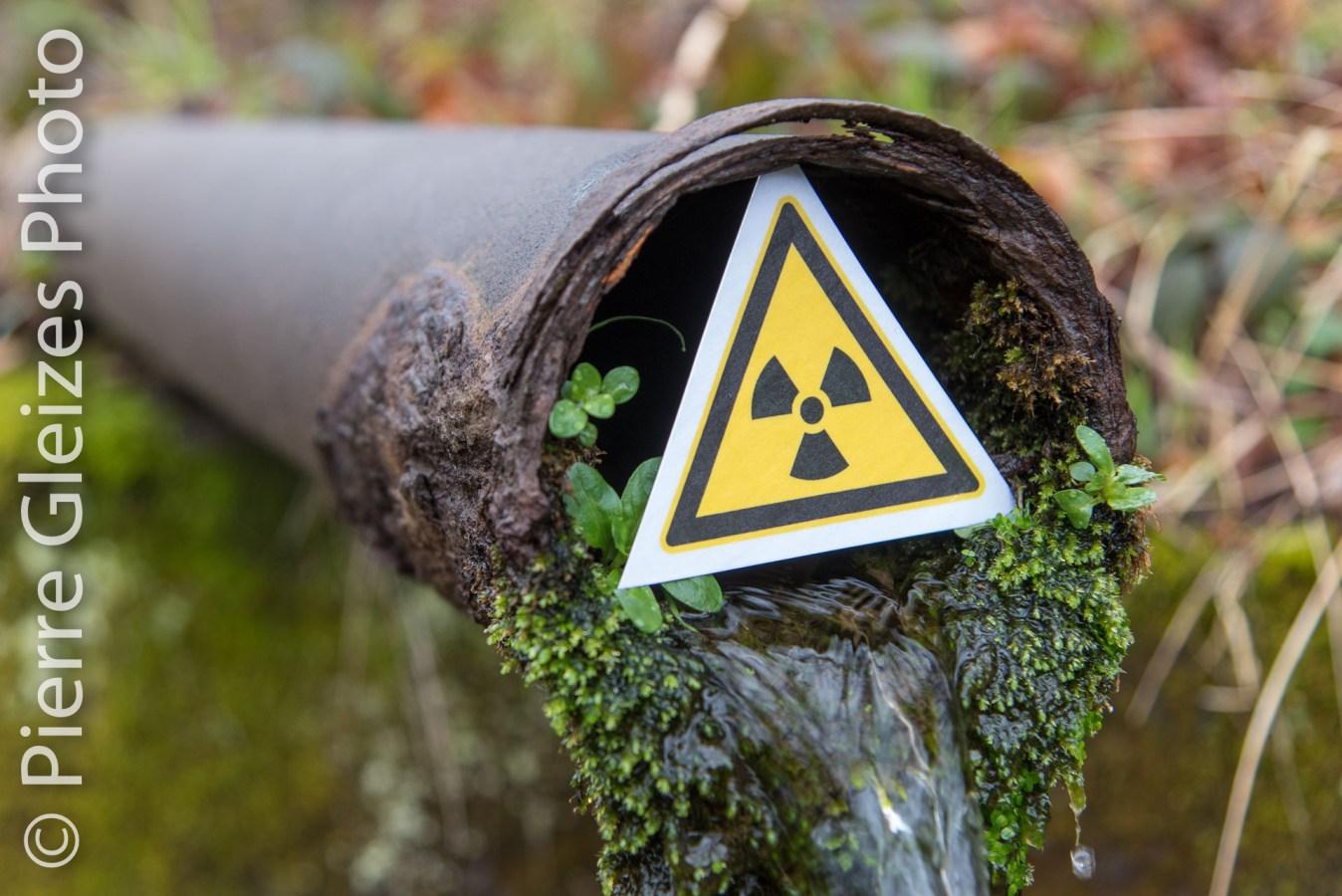 Rejet du drain numéro 6  sous le lac artificiel qui recouvre 1,3 million de tonnes de résidus contamines provenant de la mine d'uranium locale. Rapport 2015 de la CRIIRAD sur le drain numéro 6 : contamination par l'uranium 238 : 24 500 Bq/kg sec soit une valeur 230 fois supérieure a` celle relevée en amont du site de stockage. Exploitation CEA COGEMA AREVA, histoire de la bombe atomique et de l'industrie nucléaire. Le barrage digue de 42 mètres de hauteur n'est pas aux normes Grands Barrages. Le symbole de radioactivité a été place par le photographe.