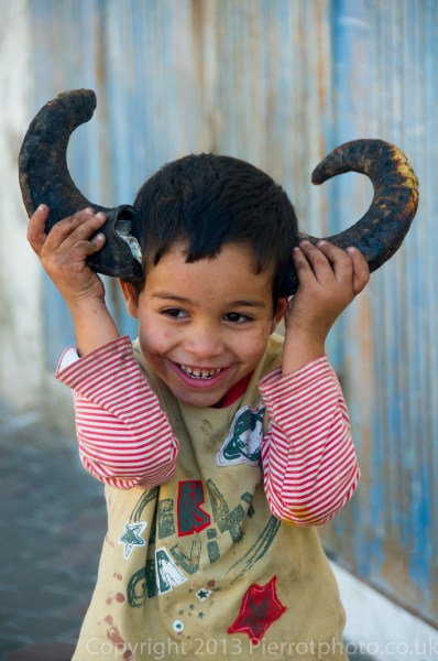 Moroccan child playing with the horns of a slaughtered sheep in Essaouira, Morocco