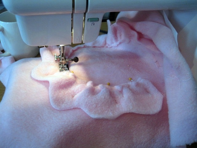 Sewing down the first strip of fleece to create the outside of the flower
