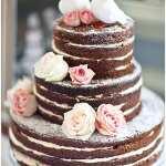 Bolo rústico de casamento de chocolare com rosas brancas e cor-de-rosa e noivinhos de topo de bolo de pombinhas. Foto: Rosie Parsons Photography.