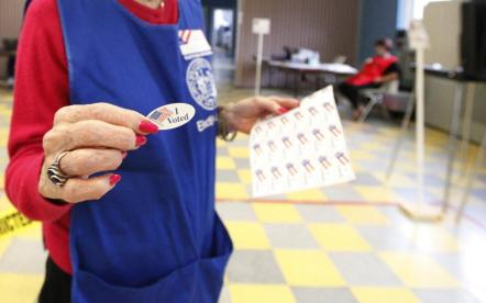 """woman handing out """"I voted"""" stickers at polling station"""