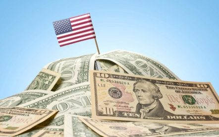 The national flag of USA sticking in a pile of american dollars.(series)
