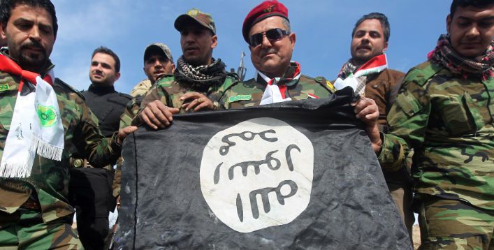 Volunteer Shiite fighters who support the Iraqi government forces in the combat against the Islamic State group, hold a black Islamist flag allegedly belonging to IS militants in the village of Fadhiliyah. Image: Ahmad Al-Rubaye / AFP