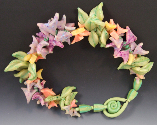 """Lindly Haunani, Crayon Lei in Oranges and Greens, 1998, 8 11/16""""  x  8 11/16"""" x 1 3/4"""", polymer, crayons, nylon.  collection of Racine Art Museum"""